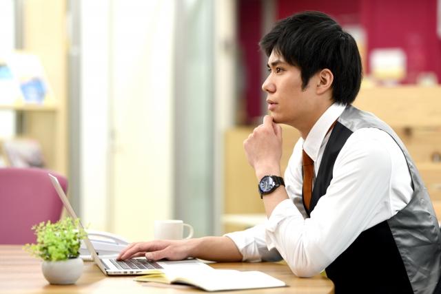 パソコン上で投資先を考えている男性