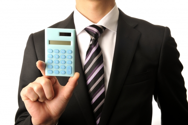 電卓で計算する男性